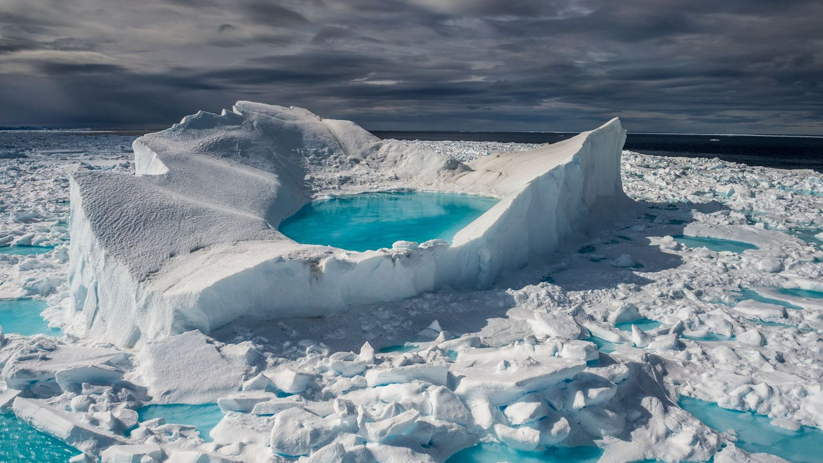Off the north coast of Canada's Baffin Island, a June sun transforms snow and ice into ...