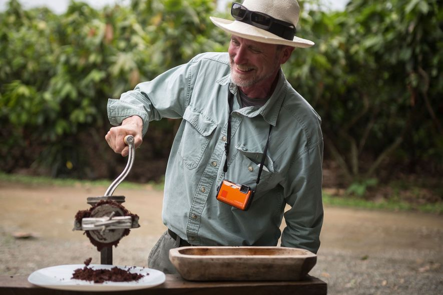 A man grinds cocoa beans in a clearing.