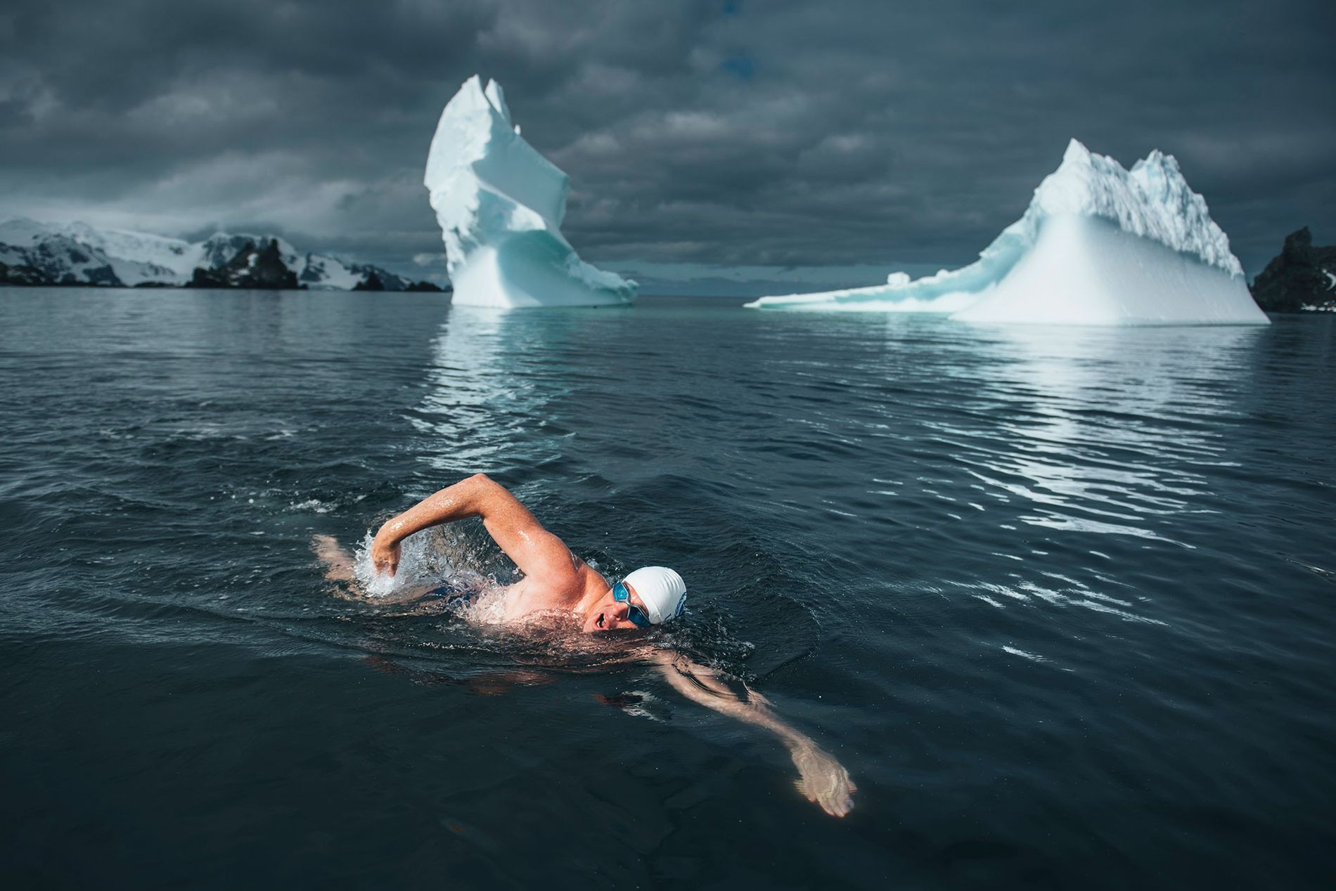 Lewis Pugh, accompanied by icebergs, swims in near-freezing Antarctic waters.