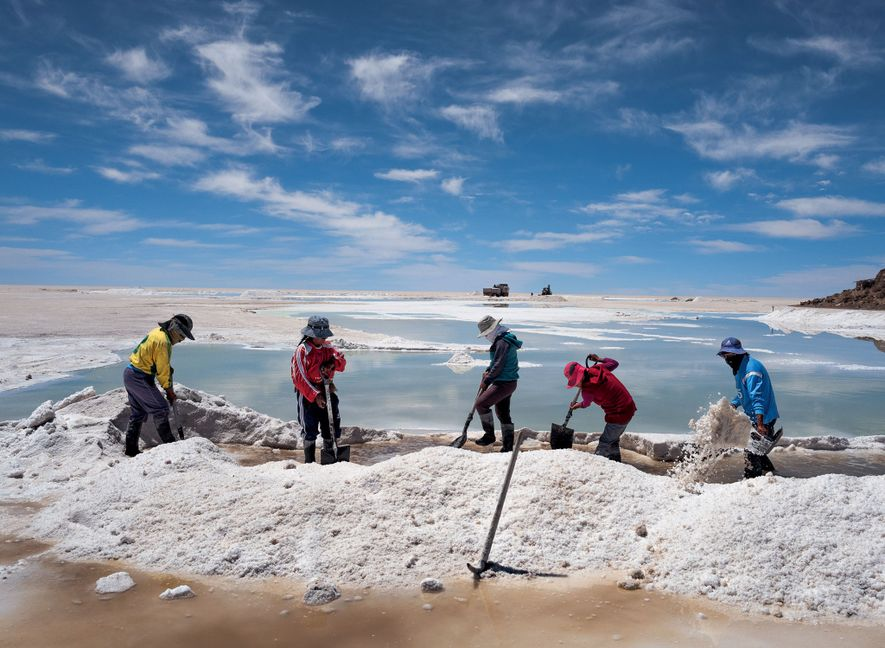While the indigenous Aymara population harvests and sells salt crusted on the surface of the Salar ...