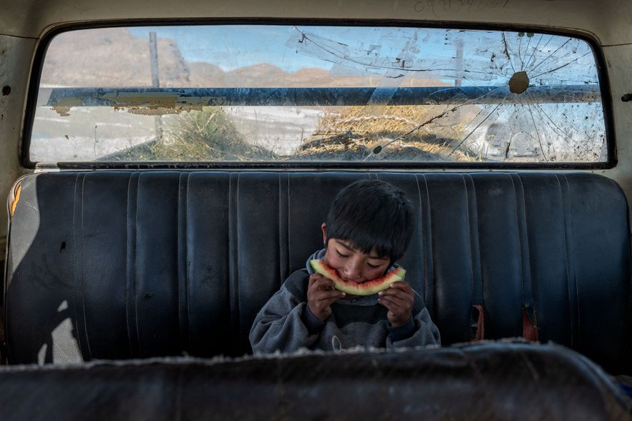 Angelo Martín Flores Chambi takes a break for a snack in his family's Chevy pickup while ...