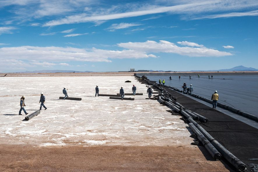 To create an evaporation pool at the lithium pilot plant in the Salar, workers roll out ...