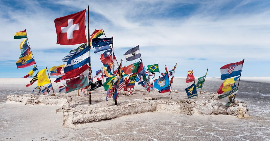 Flags left by tourists from around the world flutter in the wind on the Salar. Drawn ...