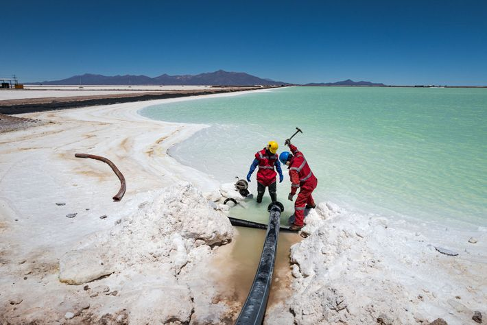 Workers at the lithium pilot plant use hammers to break up a layer of salt that ...