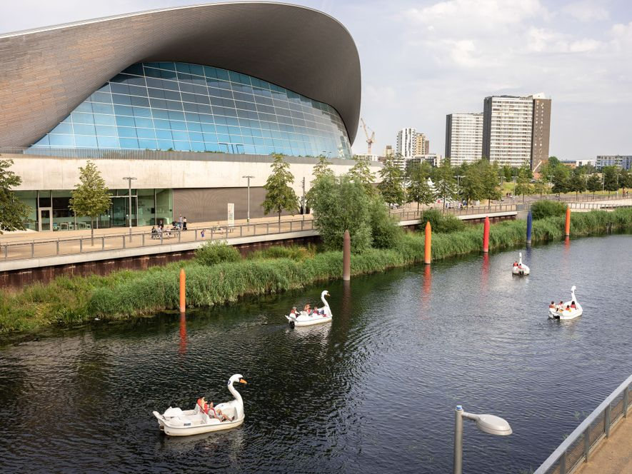 Pedal boats cruise past the London Aquatics Centre, an Olympic venue now open to the public. ...