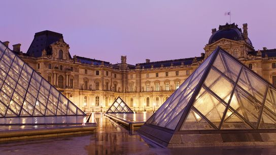 The Louvre's main entrance is illuminated at night. The world's biggest art museum, the Louvre was ...