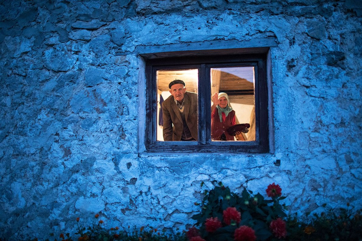 A couple peers out of their house in Lukomir.