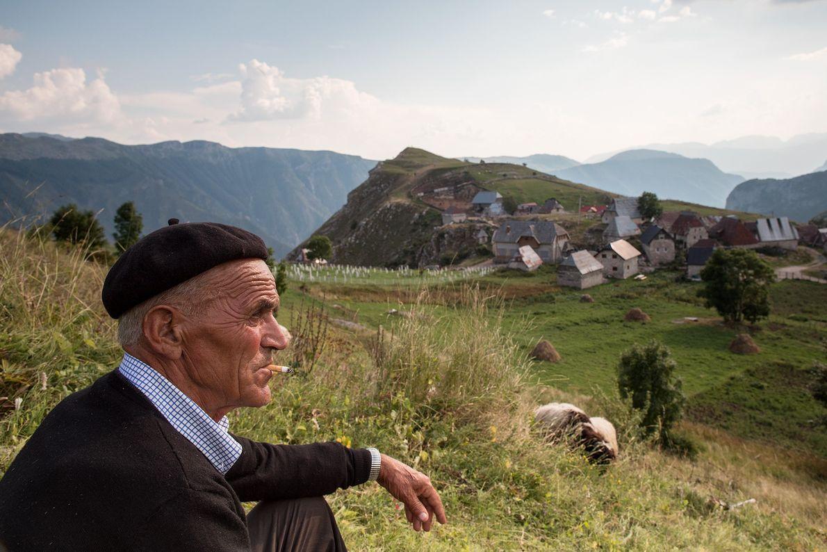 A man takes a cigarette break with a view outside Lukomir.
