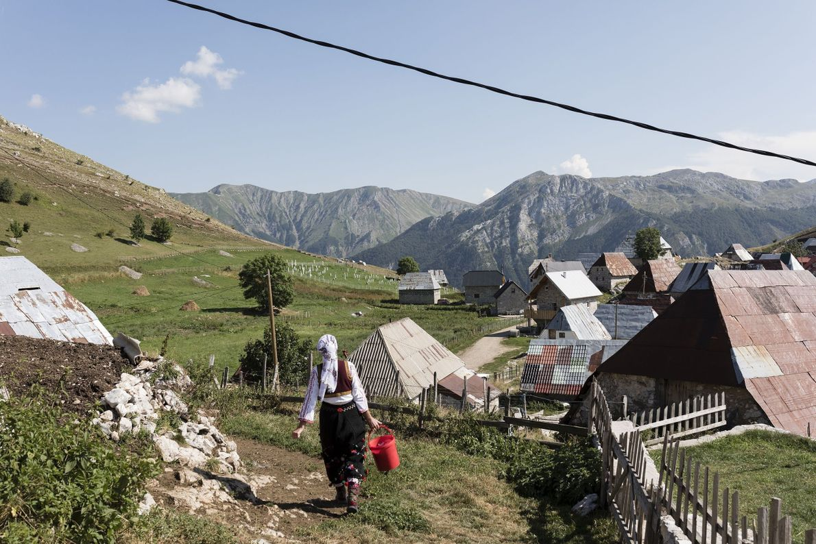A woman walks through the village to start her chores.