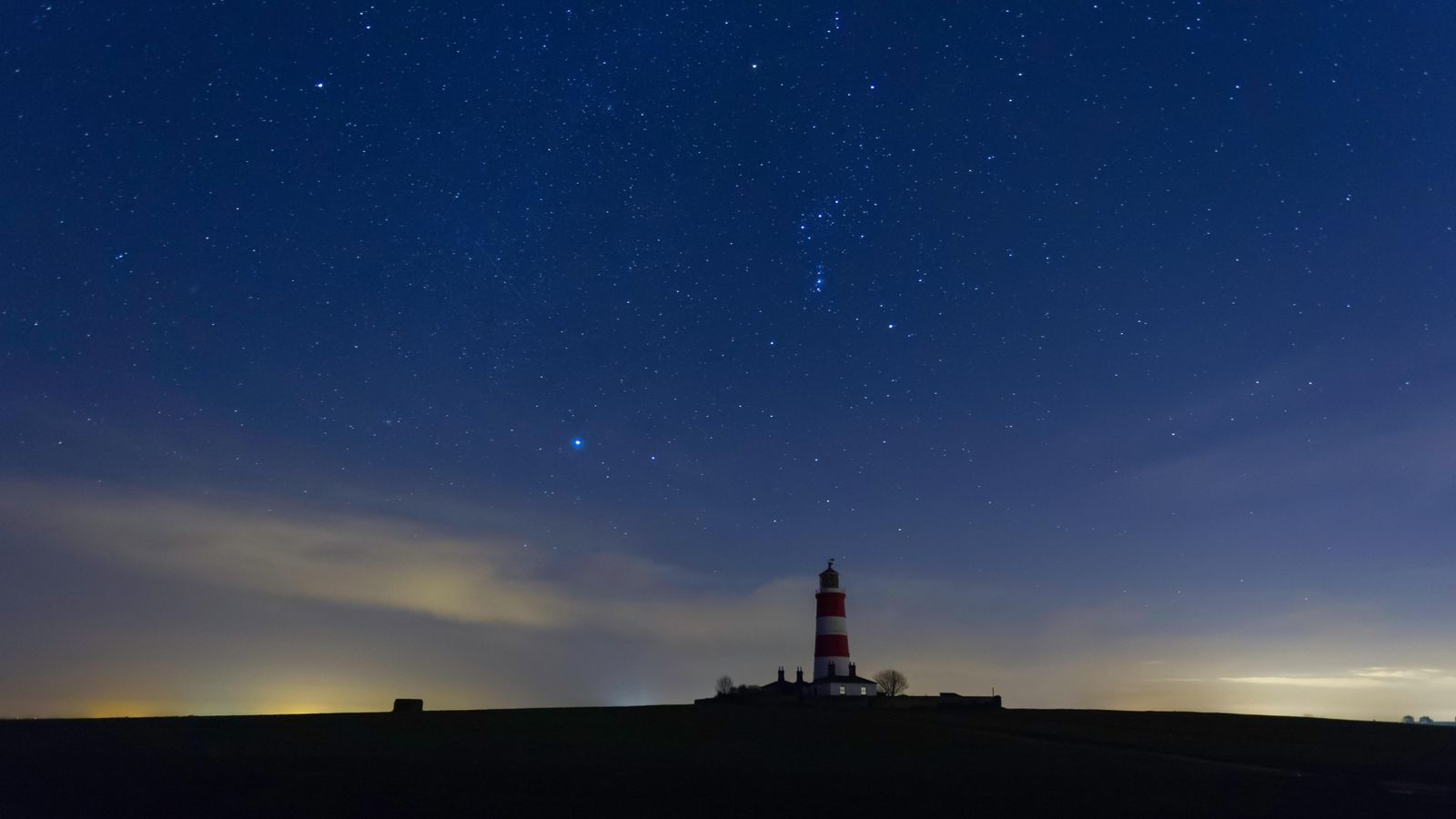 Happisburgh lighthouse in Norfolk, with the constellation of Orion directly above it. In the corners of ...
