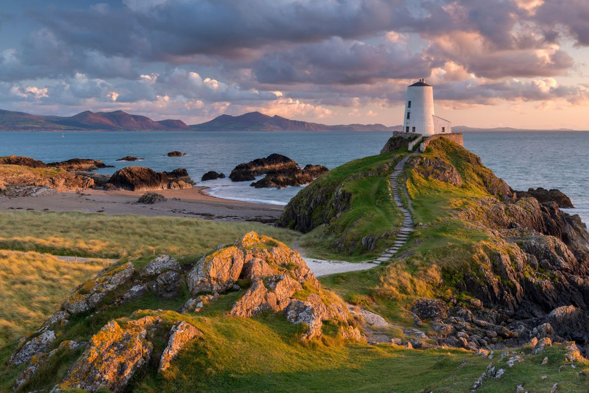 Twr Mawr lighthouse on Llanddwyn Island, off the coast of Anglesey, overlooks the mainland. The stretch ...