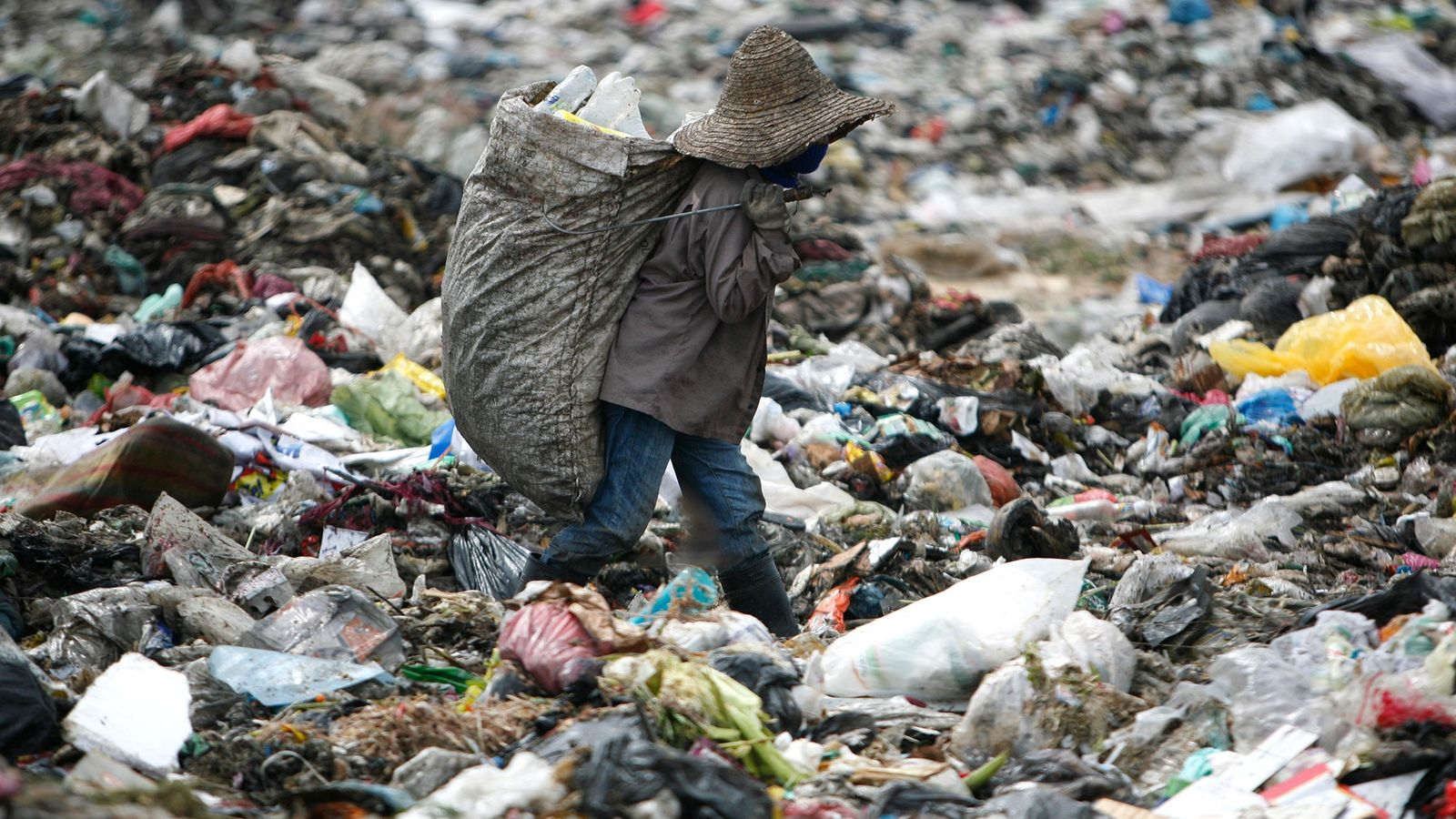 A man looks for plastic to recycle at a garbage site in Malaysia.