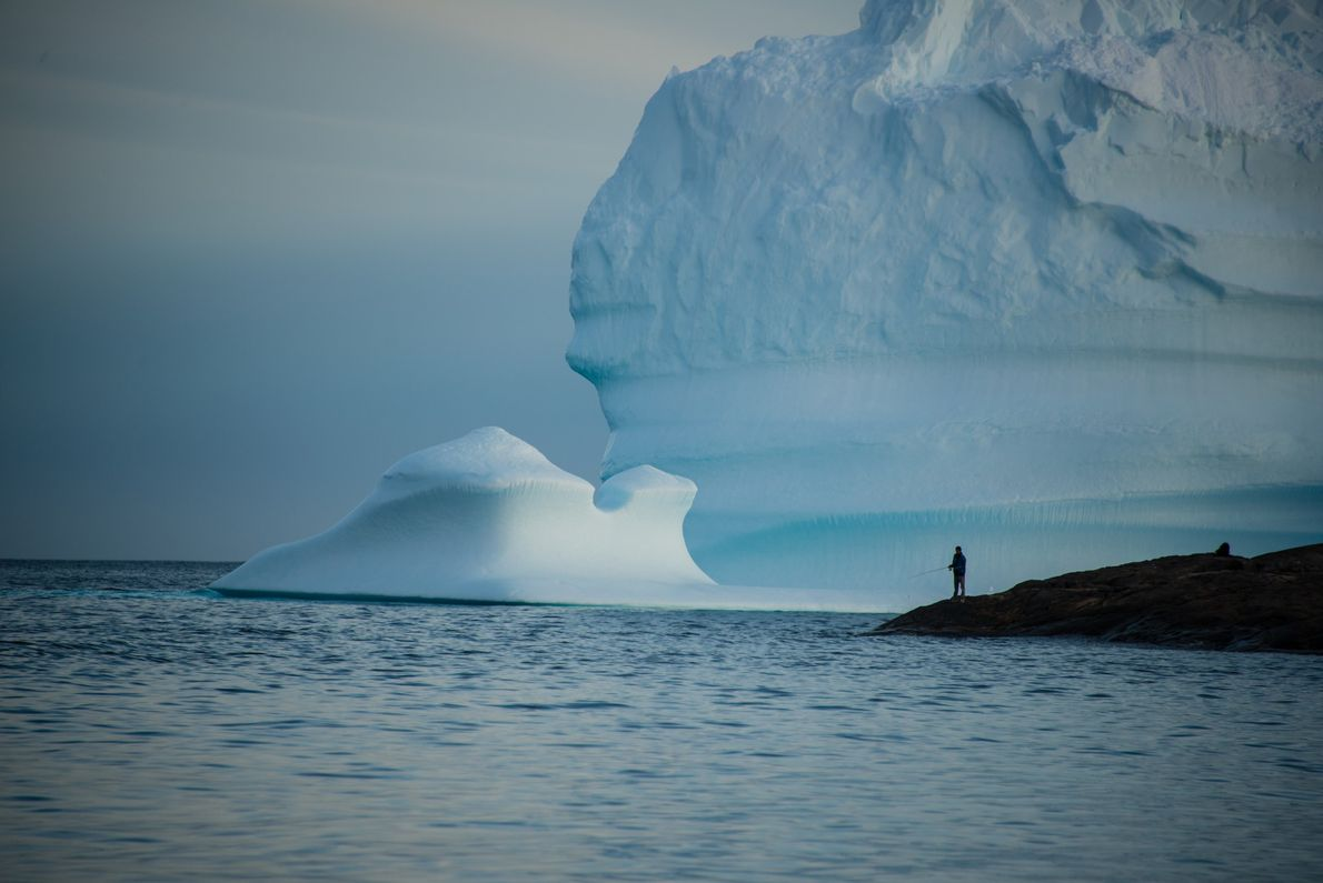 A fisherman casts a line off southeastern Greenland's shore. The island's rivers and lakes are fertile ...