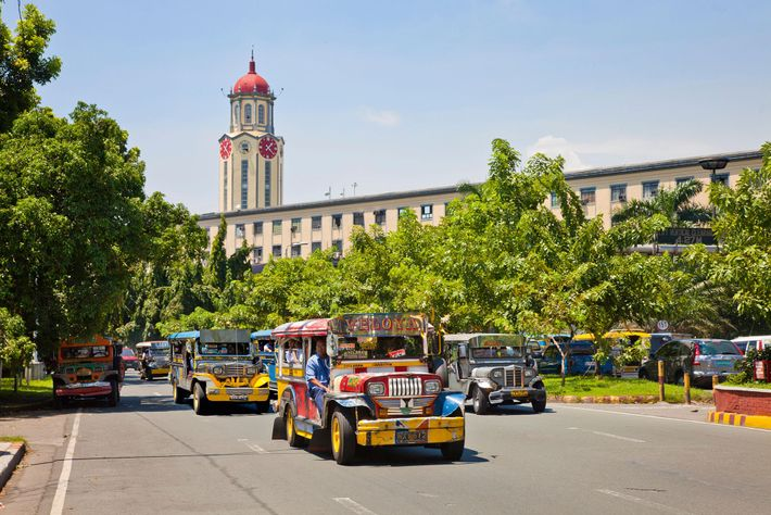Jeepneys driving past Manila's City Hall.