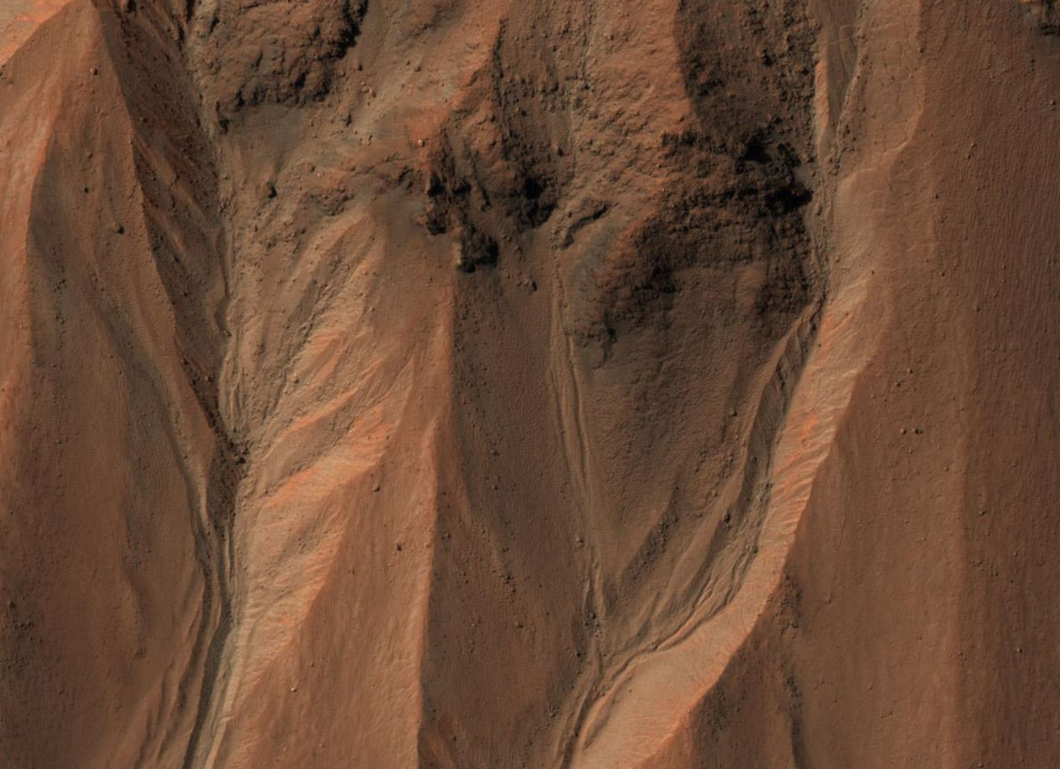 Gullies fringe the edge of southern Mars's Hale crater. On Earth, these structures usually form through ...