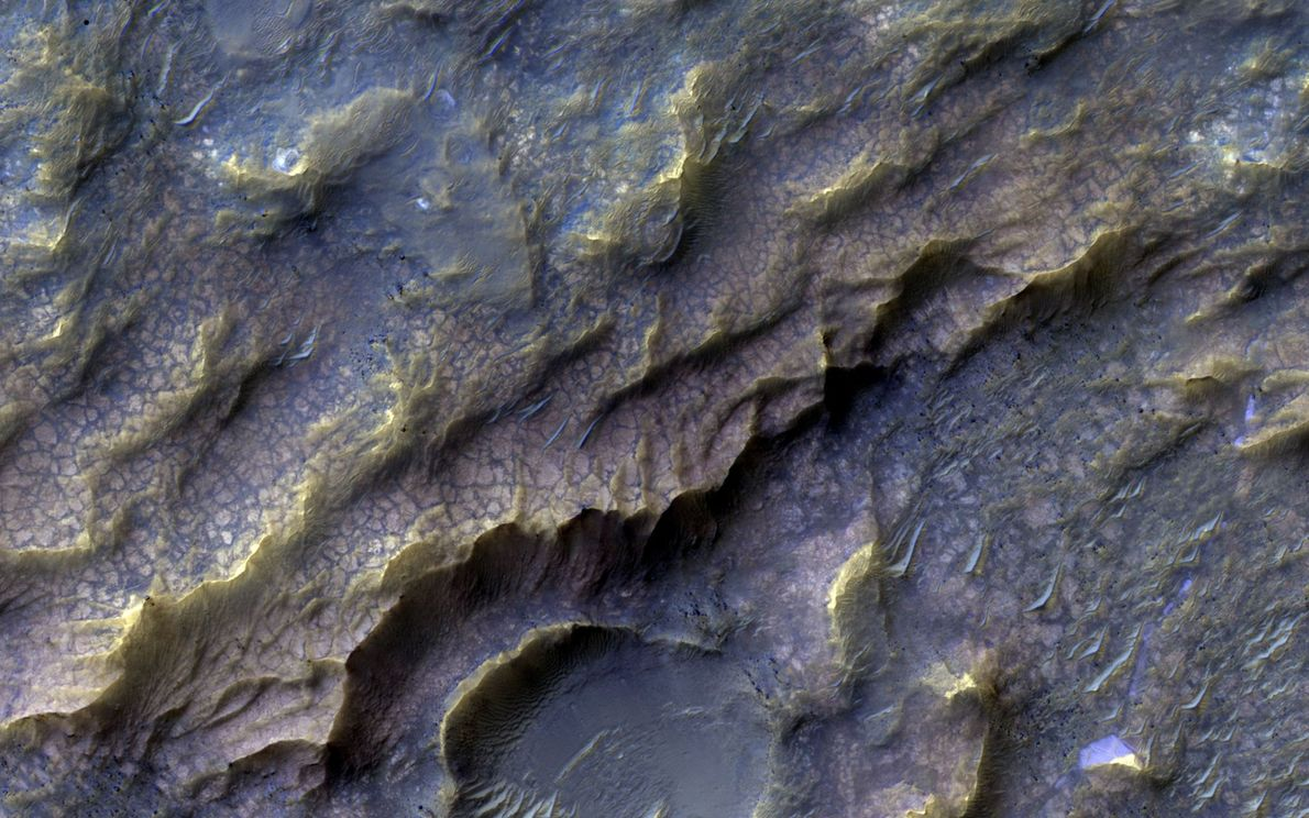 The pinkish, scaly texture is Martian bedrock that water altered long ago, forming clay-bearing rocks. It's ...
