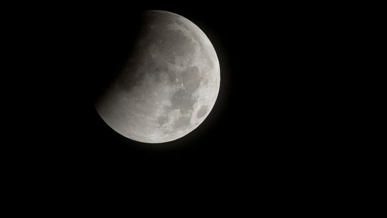 Earth's shadow darkens the moon at the start of a total lunar eclipse in December 2010.
