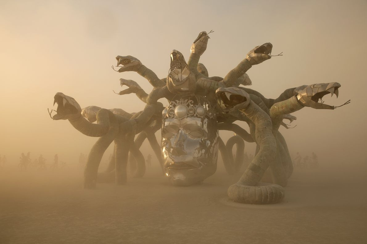 The sun sets at the Medusa head installation, as visitors around the statue ironically appear to ...