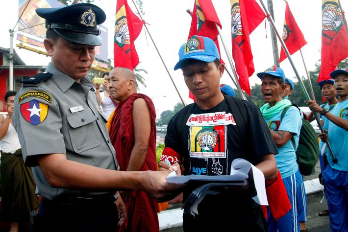 A protester shows a document to a police officer during a march against the Myitsone dam ...