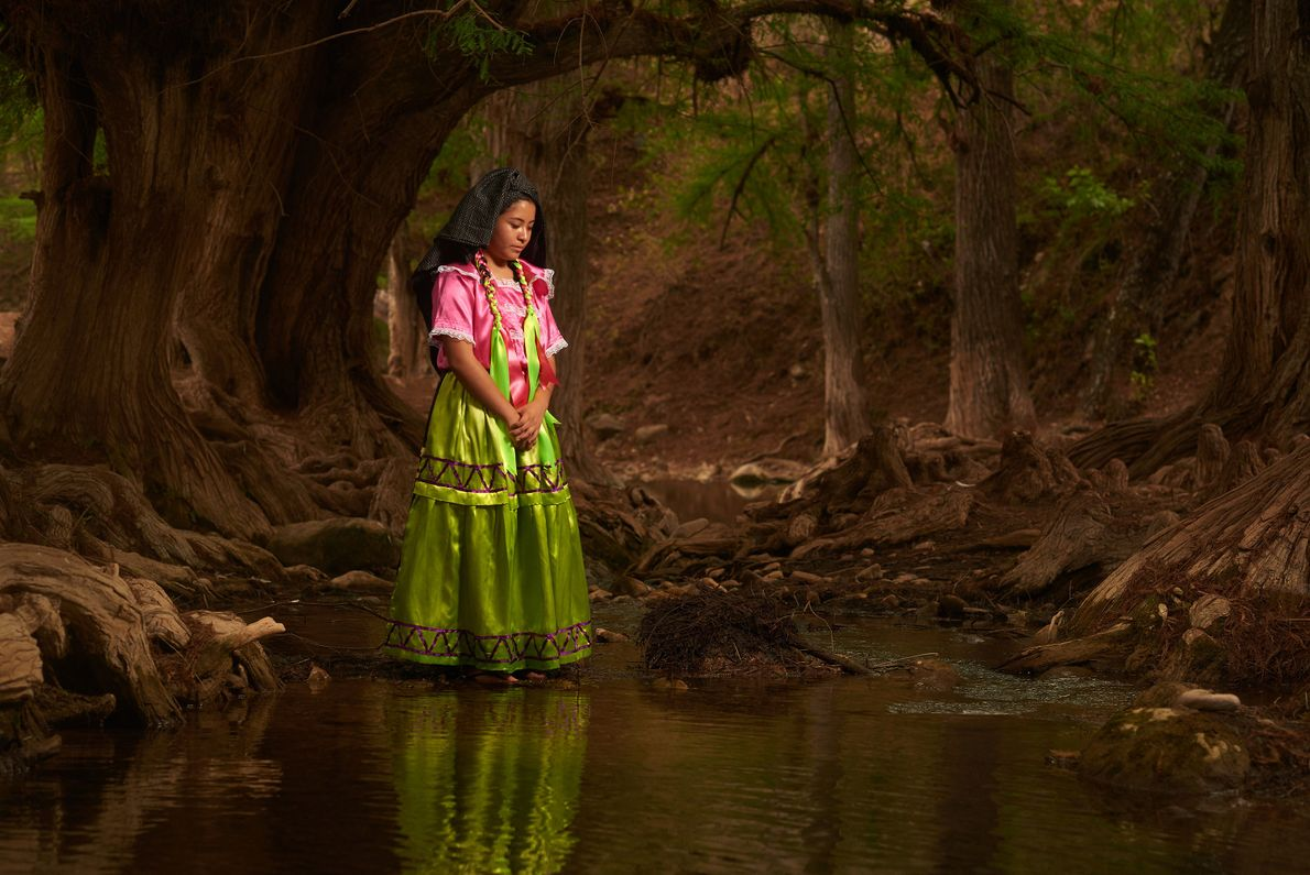 A woman, wearing traditional dress, looks down at the river of Ahuehuetes.