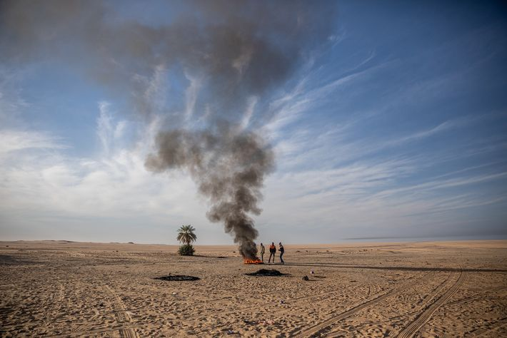 Stuck in the desert after their truck broke down, these migrants burn a tire to keep ...