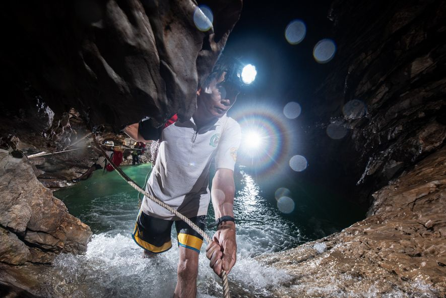 Local porters ferry the expedition team's equipment across an underground river to reach various chambers within the cave system.