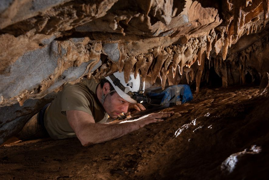 Author Neil Shea squeezes through a passage to enter a previously unknown chamber the team had discovered just days before.