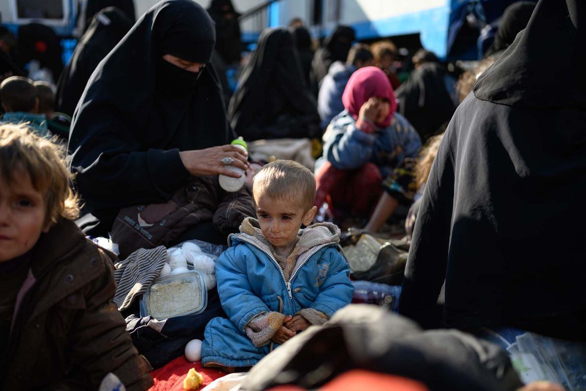 One-year-old Fatima looks at her mother as she pulls out a piece of bread. Severely malnourished, ...
