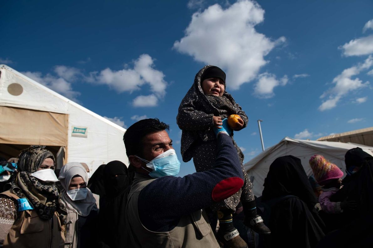 An aid worker holds up a lost child as thousands of women and children from Syria, ...