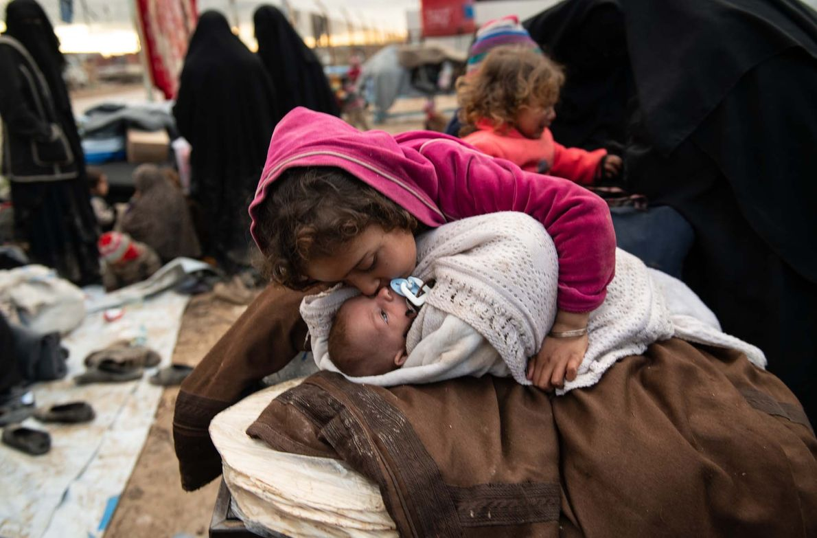 Noor, 7, kisses her baby brother, Abdullah, one month old, as she watches over him in ...
