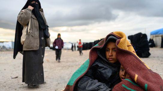 Mohammed Khalaf, 7, holds his little brother, Diyab, at the al-Hol refugee camp.