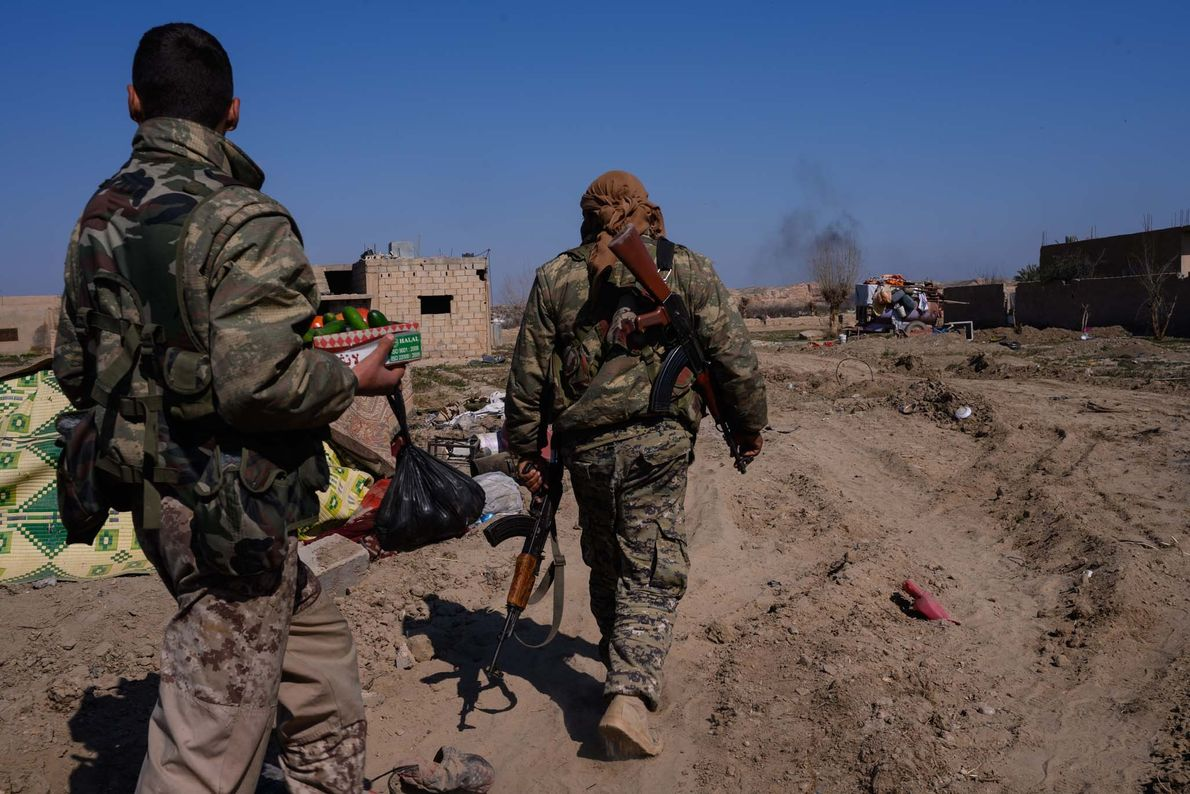 Fighters with the Syrian Defence Forces walk through the tent camp abandoned by ISIS militants only ...