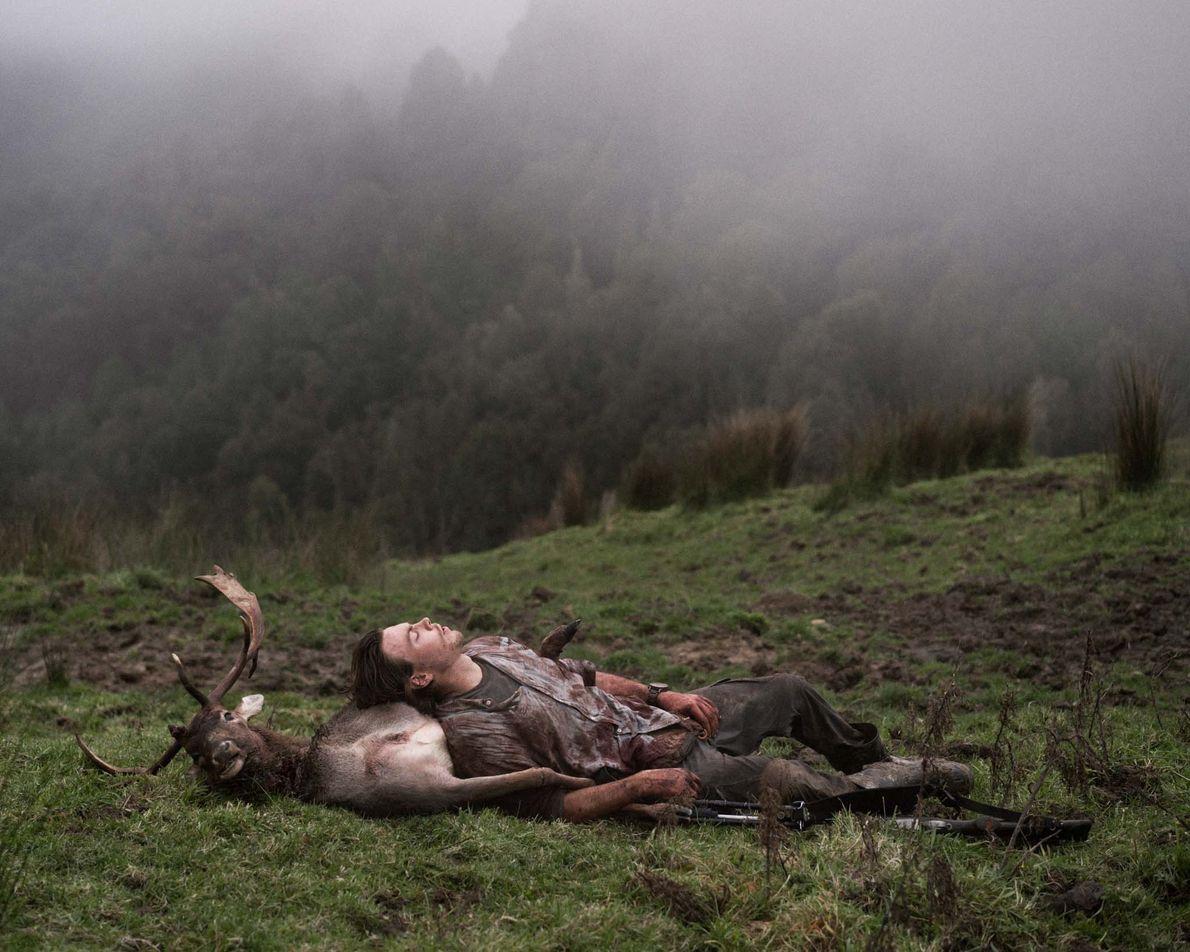 Recreational hunter Jack Cashmore takes a break while carrying a deer carcass up a hillside near ...