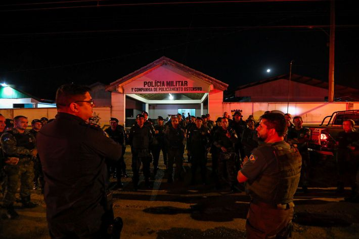 At the start of the operation, IBAMA agents confer with military police outside police headquarters in ...