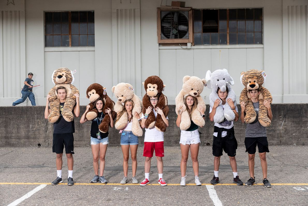 A group of friends, including three sets of twins, show off the stuffed animals they won ...