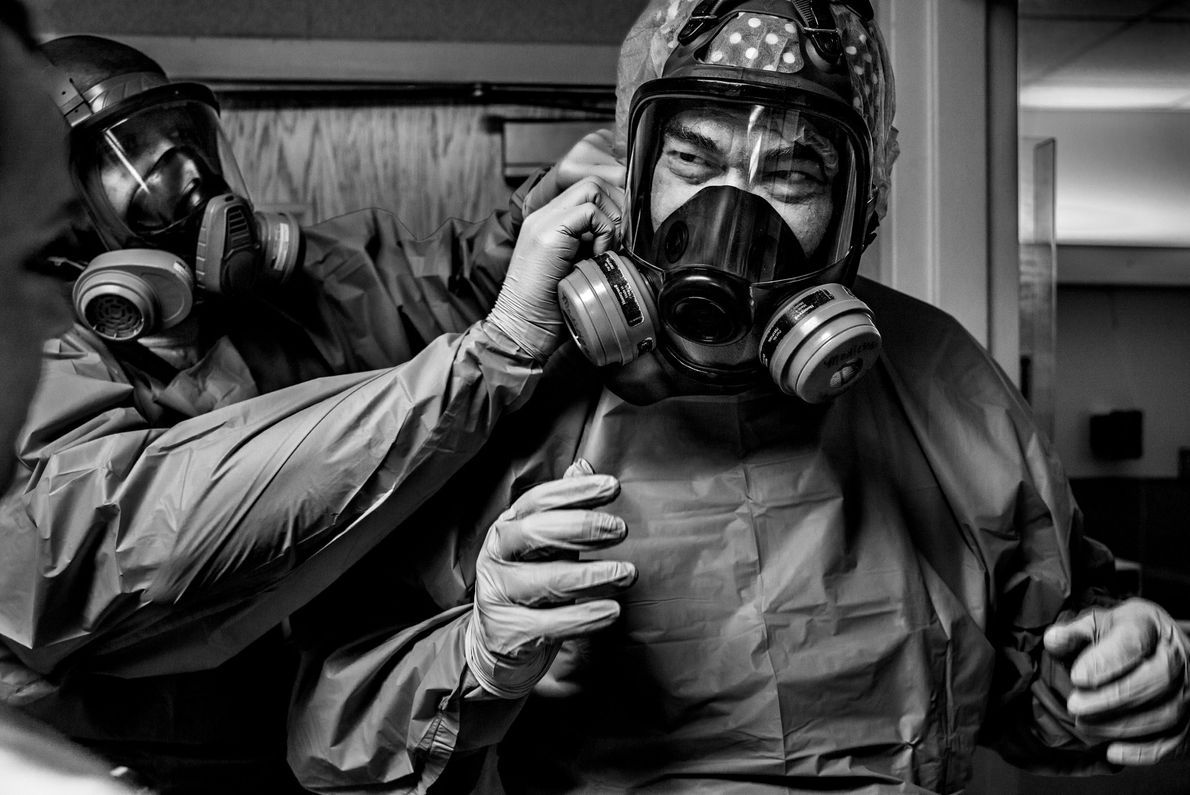 Physician Gerald Foret (at right) dons a protective mask before seeing COVID-19 patients at Our Lady ...