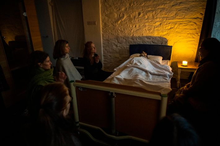 Six women caretakers and loved ones share in a moment of meditation as they surround the ...