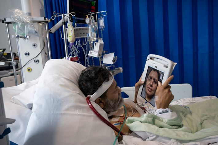 COVID-19 Patient, Foysal Ahmad, 51, speaks with his wife Nipa Begum from the Intensive Care unit of the ...