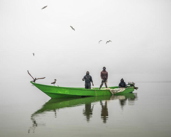 Fishermen pull in their nets at dawn on a Lake Naivasha as gulls and hamerkops fly ...