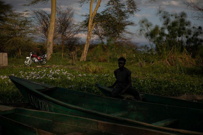 A man sits on a fishing boat at Tarambeta Beach. The vegetation behind him is an ...