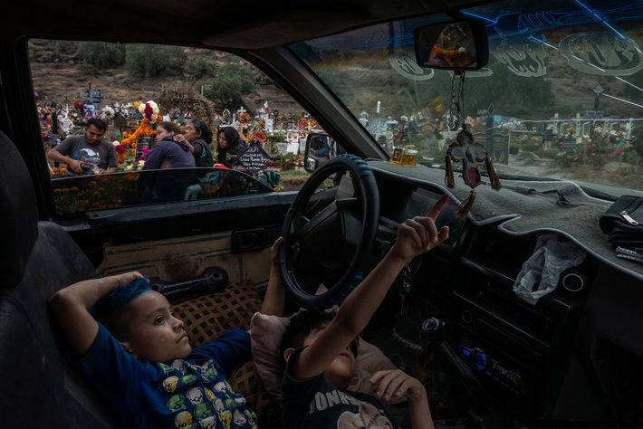 Andres and Alan wait inside their truck while their family mourns their grandfather, Eduardo Martinez, who ...