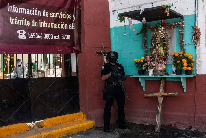 A police officer stands guard outside the Cemetery La Loma, in Tlalnepantla de Baz, Mexico, while ...