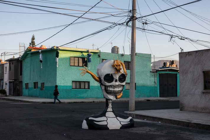 A woman passes by a sculpture made by artist Raymundo Medina in the neighborhood of Tlahuac ...