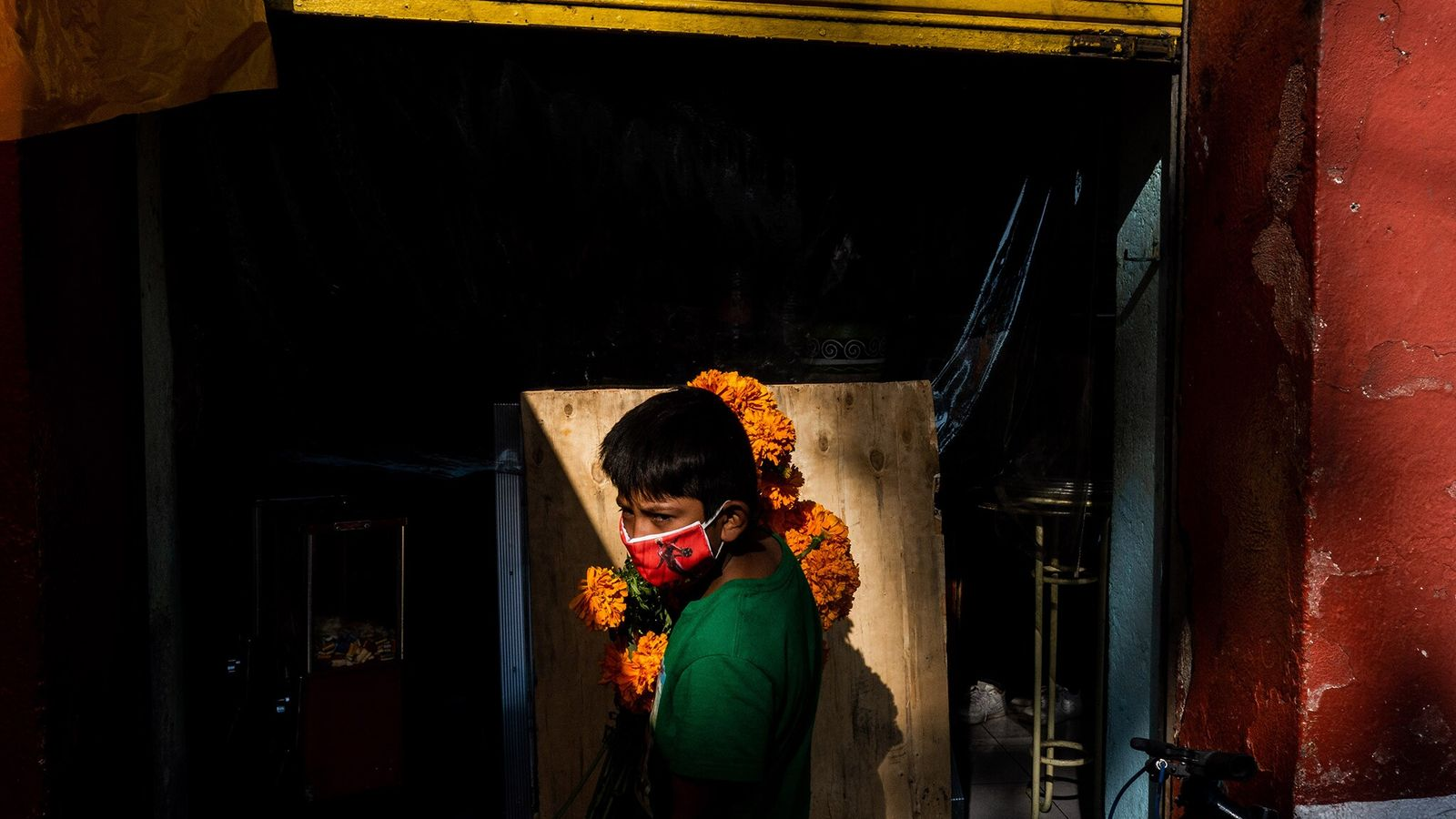 A young boy with a bouquet of marigolds waits for his mother outside a bakery as ...