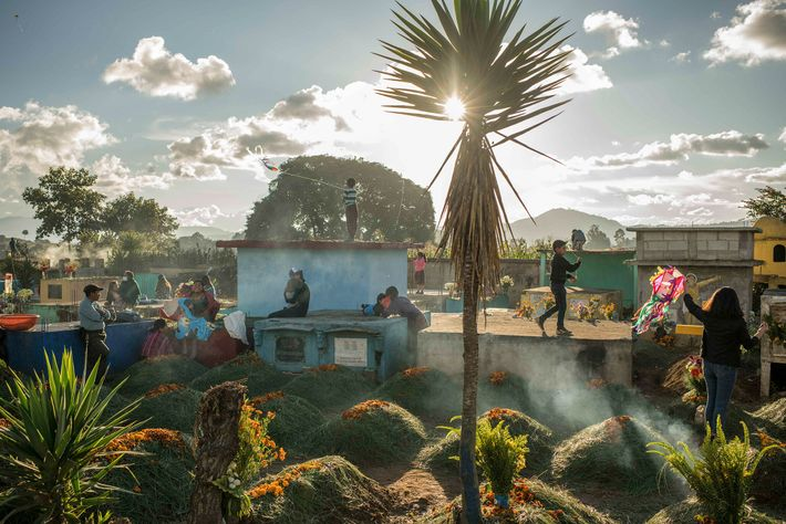 A few days before Día de los Muertos, families lingered around the tombs of their loved ...