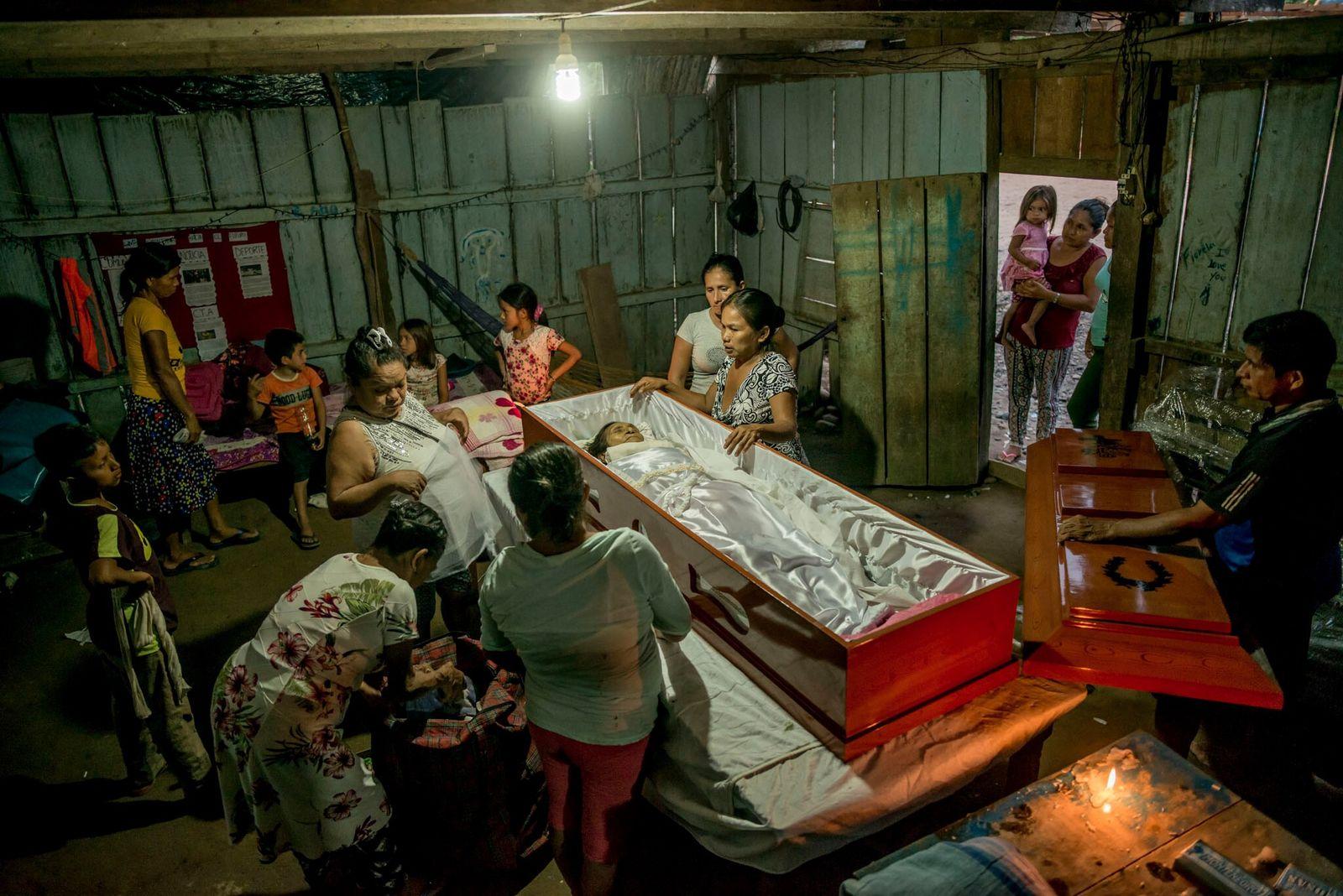 Relatives dress and prepare the body of Julia Sebastian War, a member of the Wambi tribe ...