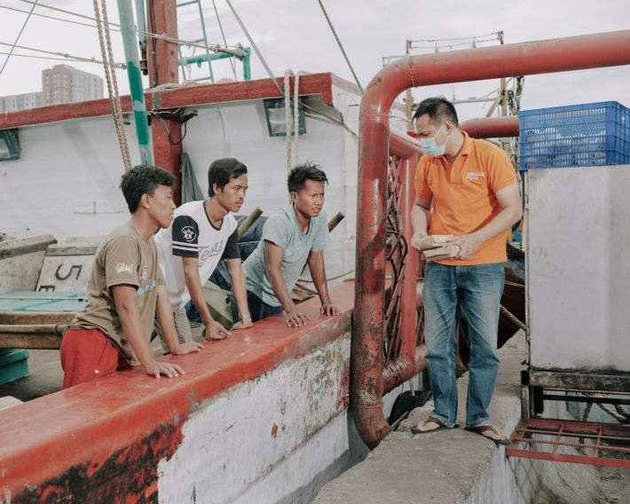 Fishermen and workers at the port of Muara Angke, a densely populated area in North Jakarta, ...