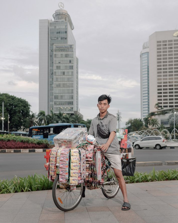Fauzi, an informal worker, sells instant coffee near Hotel Indonesia Roundabout, a popular pedestrian area in ...