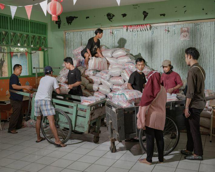 Volunteers with Foodbank of Indonesia unload and store 20 tons bags of rice in a school ...