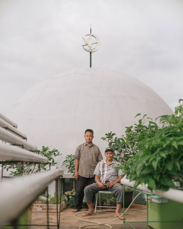 Yono, left, and Faizin pose on a rooftop farm on the fourth floor of the Baitussalam ...